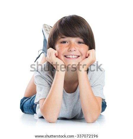 Closeup of smiling little boy with freckles lying on white background. Happy cute male child lying on white floor and looking at camera. Portrait of a smart young boy.  - stock photo