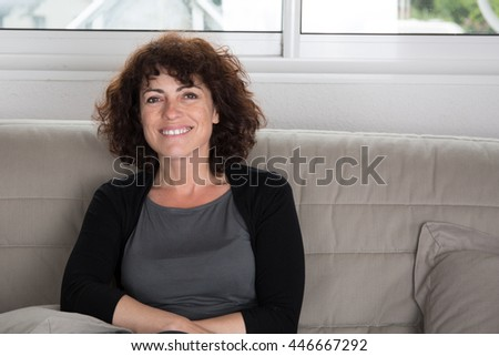Closeup of smiling middle aged woman lying on couch - stock photo