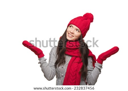 Closeup of smiling woman wearing red winter hat, scarf and mittens with opened arms looking up at blank copy space, over white background - stock photo