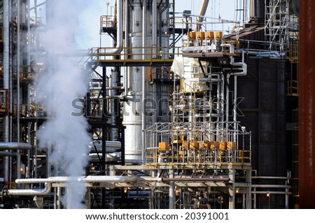 Closeup of smoke rising in front of a petrochemical plant with lots of pipes - stock photo
