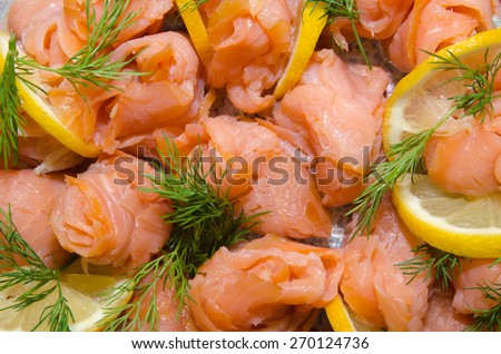 Closeup of smoked salmon rolls with sliced lemon and dill - stock photo