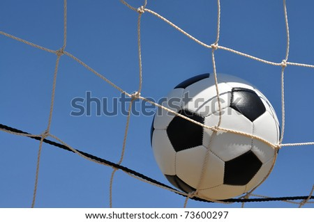 Closeup of soccer ball in net with copy space. - stock photo