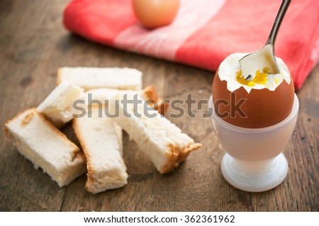 closeup of Soft boiled egg in egg cup and served with toast fingers on wooden table  - stock photo