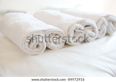 Closeup of soft white towels, rolled and piled.