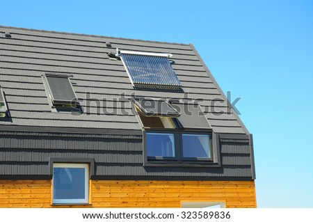 Closeup of Solar Water Panel Heating, Dormers, Solar Panels, Skylights, Ventilation and Air Conditioning Systems Installed on House Roof. Energy Efficiency New Passive House Building Concept.  - stock photo