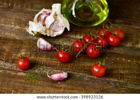 closeup of some cherry tomatoes, some garlic cloves and a glass cruet with olive oil on a rustic wooden table - stock photo