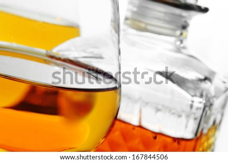 closeup of some cognac glasses with liquor and a vintage glass liquor bottle in the background