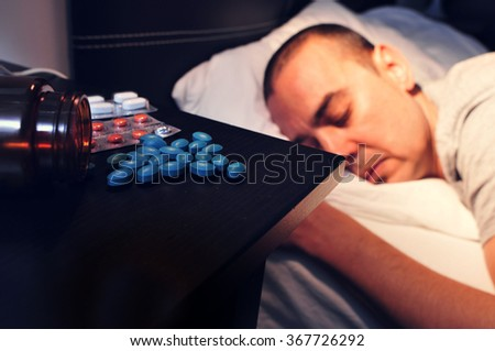 closeup of some different pills in the nightstand and a young man laying face down in bed with his eyes closed, at night - stock photo