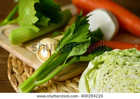 closeup of some different raw vegetables, such as carrots, parsnips, turnips, cabbage and celery, on a rustic wooden table - stock photo