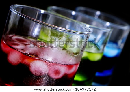 closeup of some glasses with cocktails of different colors in a club - stock photo