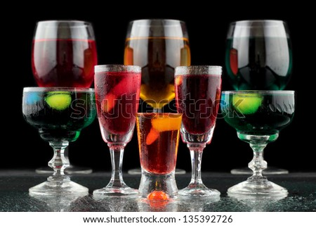 closeup of some glasses with cocktails of different colors in nightclub - stock photo