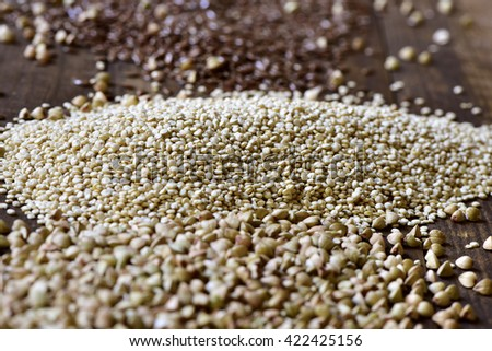 closeup of some piles of different edible seeds such as buckwheat, quinoa or brown flax on a rustic wooden table - stock photo