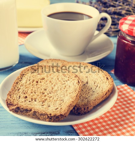 closeup of some toasts in a plate, a cup of coffee, a bottle with milk and a jar of jam on a rustic blue wooden table, with a cross-process effect - stock photo