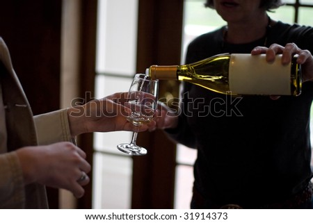 Closeup of some wine glasses being poured during a wine tasting. - stock photo