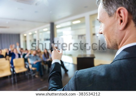 Closeup of speaker pointing to audience on business conference in meeting hall - stock photo