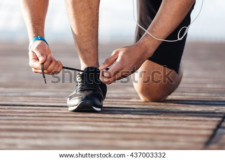 Closeup of sportsman laces his sneakers on pier - stock photo