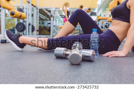 Closeup of sporty woman resting sitting on the floor of fitness center and female friend doing exercises with dumbbells in the background. Selective focus on a dumbbells. - stock photo