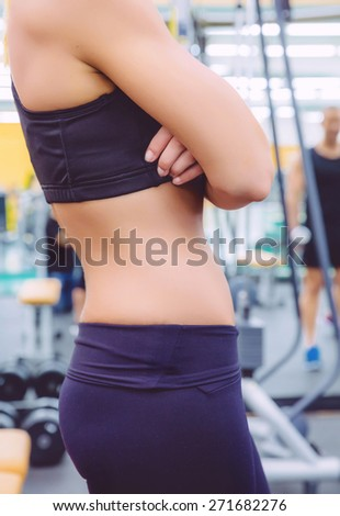 Closeup of sporty woman with slim waist and black sportswear over a fitness center background. Health and training concept. - stock photo