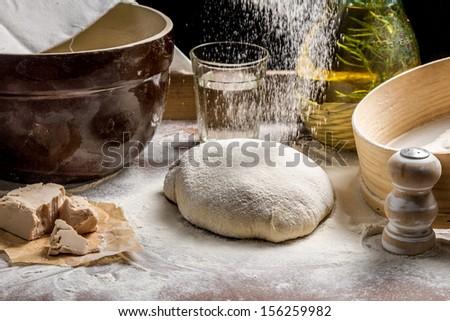 Closeup of sprinkling flour pizza dough - stock photo