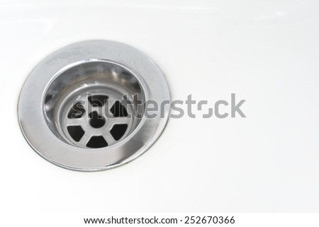 Closeup of stainless steel drain of white washbasin background - stock photo
