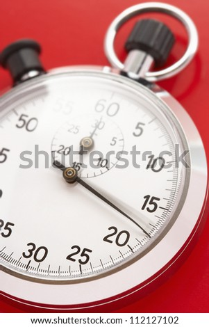 Closeup of stopwatch over red background - stock photo