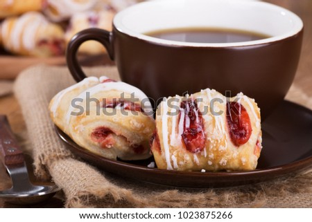 Closeup of strawberry pastries and cup of coffee with plate of pastries in background