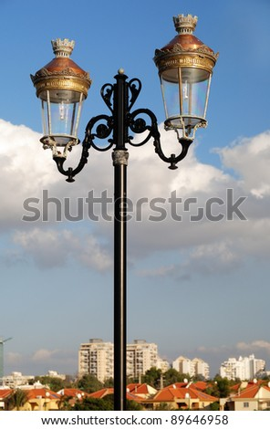 closeup of streetlight over blue sky with clouds