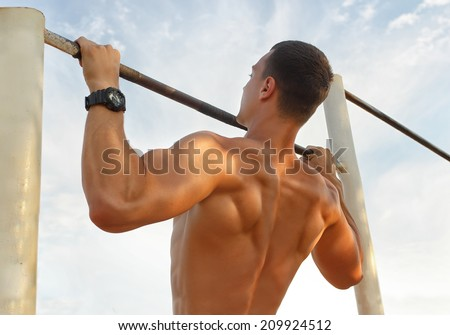 Closeup of strong  athlete doing pull-up on horizontal bar.Mans fitness with blue sky in the background and open space around him - stock photo