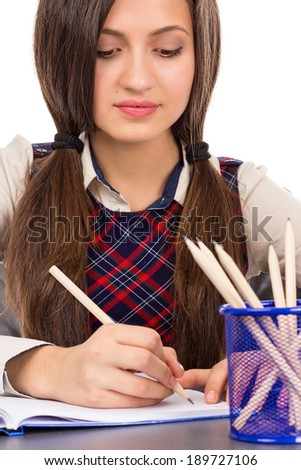 Closeup of  student sitting at her desk concentrated and doing her homework isolated over white background