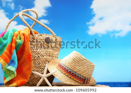 Closeup of summer beach bag and straw hat on sandy beach. - stock photo