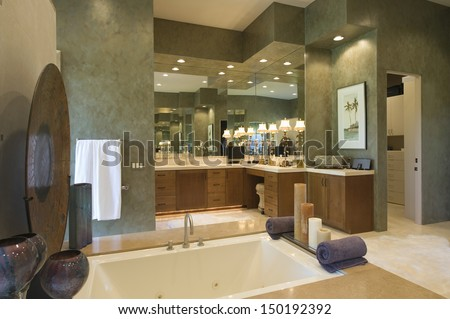 Closeup of sunken bath with cabinets and mirror in background at bathroom in home - stock photo
