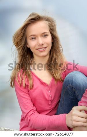 Closeup of teenage girl sitting on a school bench - stock photo