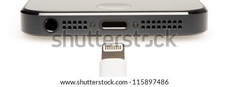 Closeup of the charging port on the bottom of a smartphone, with the charging connector in the foreground. - stock photo