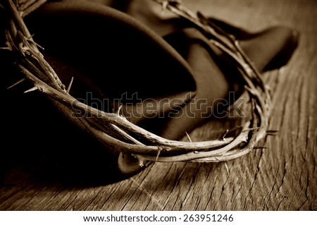 closeup of the crown of thorns of Jesus Christ on a rustic wooden surface, in sepia toning - stock photo