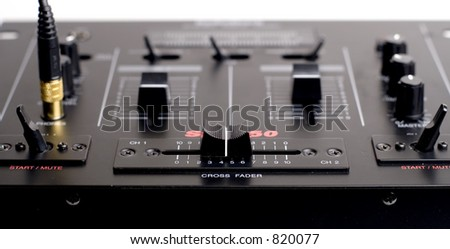 Closeup of the DJ crossfader/Mixer w/ headphones plugged in - stock photo