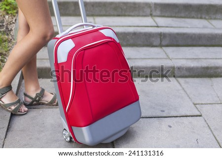 Closeup of the feet of a young girl near red travel suitcase. - stock photo