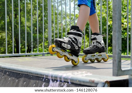 Closeup of the feet of a young girl wearing rollerblades standing on top of a ramp at a skate park while out roller skating - stock photo