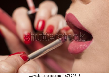 Closeup of the fingers of a female beautician or makeup artist applying lipstick to the lips of a model - stock photo