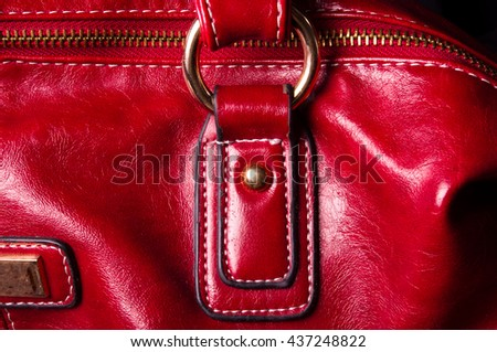 closeup of the fittings on the red leather hand bag