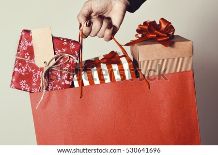 closeup of the hand of a young caucasian woman with her fingernails painted red holding a red shopping bag full of gifts wrapped in different papers