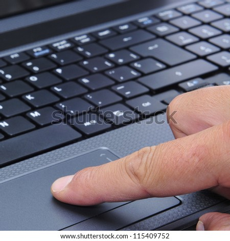 closeup of the hand of someone who is working with a laptop
