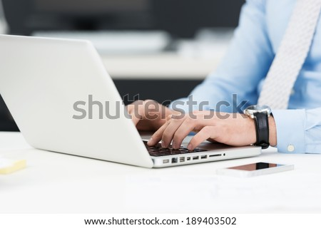 Closeup of the hands of a businessman working on a laptop computer as he sits at his desk - stock photo