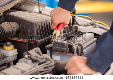 Closeup of the hands of a mechanic using jumper cables to start a car - stock photo