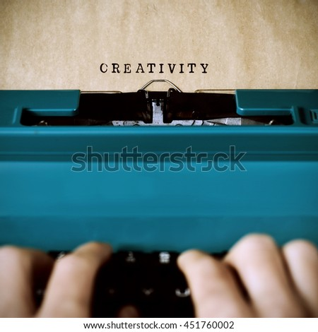 closeup of the hands of a young man typewriting the word creativity in a yellowish foil with an old blue typewriter - stock photo