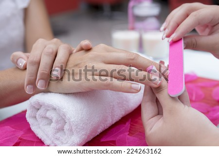 closeup of the hands of a young woman receiving the nail file by a beautician at the beauty salon - focus on the middle finger - stock photo