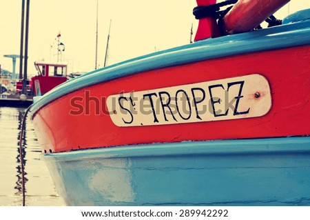 closeup of the hull of a boat  moored in Saint-Tropez, France, with the text St. Tropez written in it - stock photo