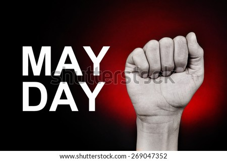closeup of the raised fist of a young caucasian man and the text may day on a red background - stock photo
