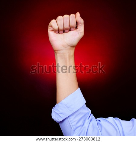 closeup of the raised fist of a young caucasian man on a black background red illuminated - stock photo
