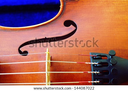 Closeup of the strings and f-hole of a beautiful violin - stock photo
