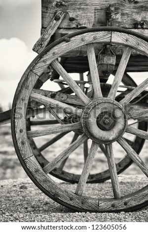 Closeup of the wheels of an old Wagon, Utah, USA. Black and white with slight sepia toning. - stock photo